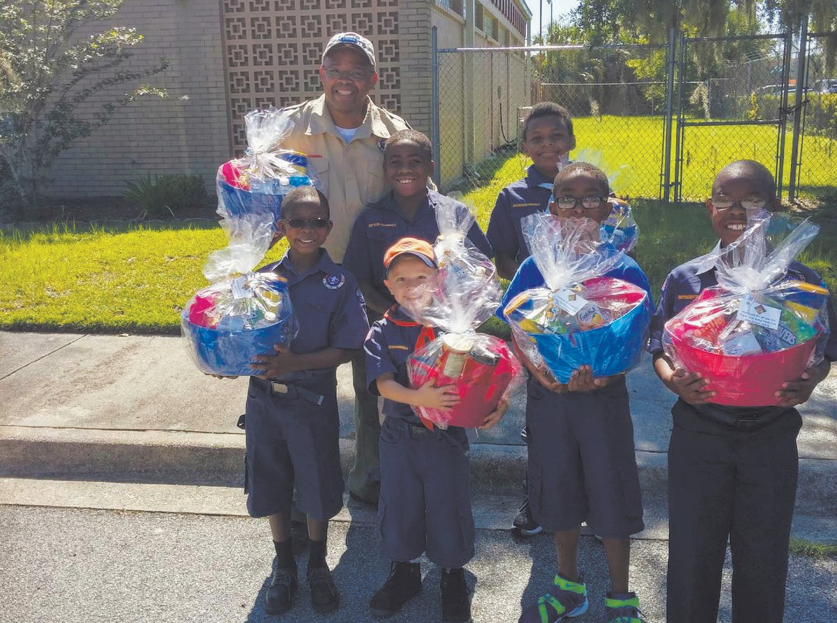 Cub Scout Leader Joseph Carter shown with Cub Scout Pack 210 members