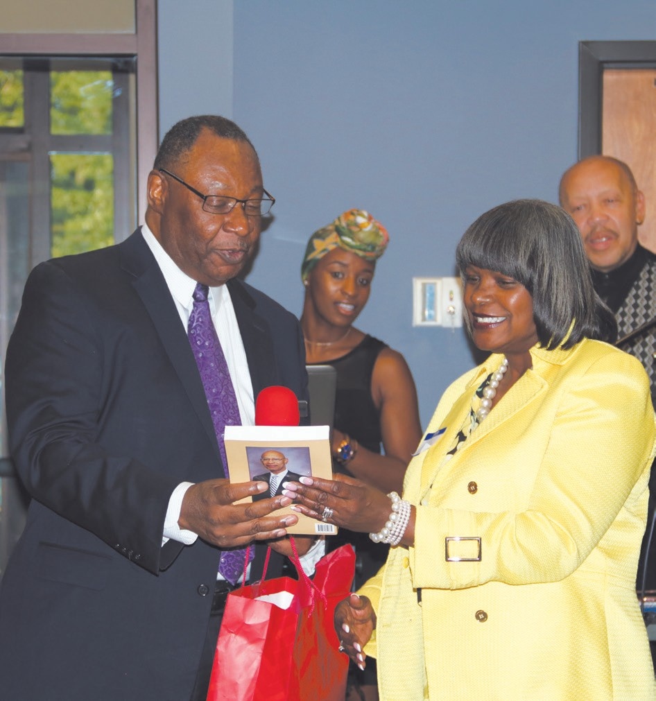 "Robert James presents COD Director, Dr. Sylvia Carey-Butler, with special gifts, including a copy of From ""N Word"" to Mr. Mayor by former Savannah Mayor Dr. Otis Johnson, who attended the reception."