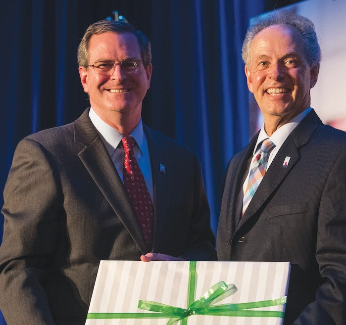 Steve Pound, (Left); presents Gregg Schroeder, President & CEO of United Way of the Coastal Empire (Right) with a retirement gift.