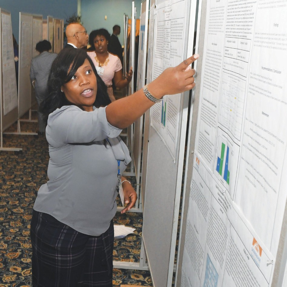Jameka Kirkland discussing her research on The Child Abuse Prevention and Treatment Act, conducted under research mentor Dr. Evelyn Denard. Photo Credit: Jason Miccolo Johnson