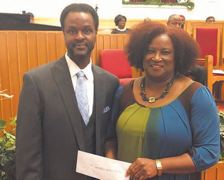 Gena Taylor, Executive Director at Greenbriar Children's Center accepts presentation from the Clergymen In Action