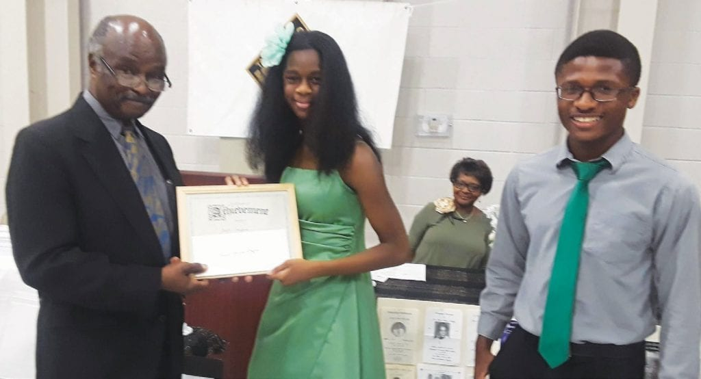 Rev. James C. Hudson presents first place prize and certificate to Jayla Griffin, essay winner. Matthew Hudson announced the winner.