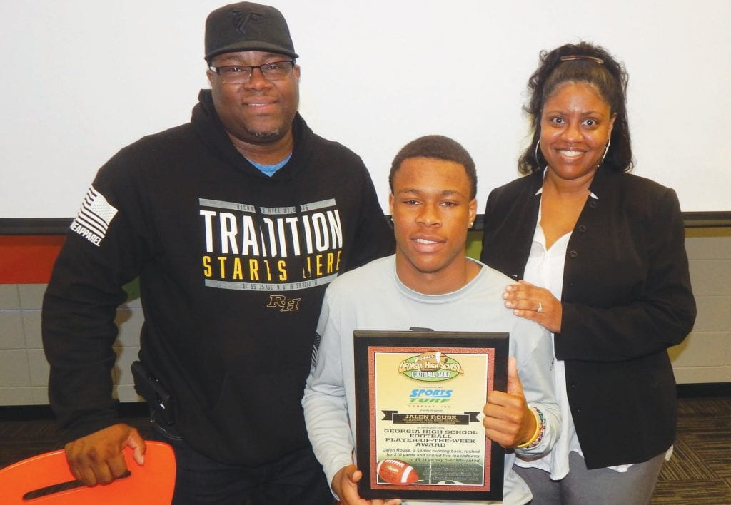 RHHS Wildcat Jalen Rouse with his parents Cedric and Charisse after winning the Georgia High School Football Statewide Player of the Week award for his dominating performance in last week's playoff game against Lanier. Photo by Mark Swendra.