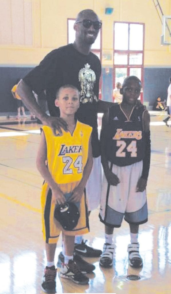 Marcus Scott (right) shown with Kobe Bryant at basketball camp